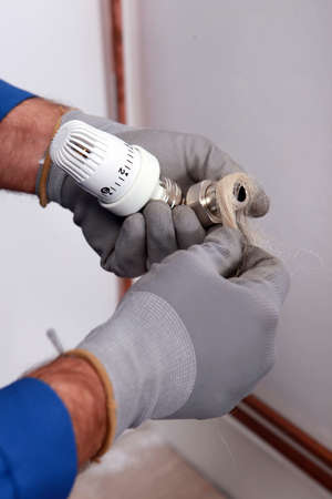 watertight: Plumber wrapping flax around the joint of a pipe and thermostatic controller Stock Photo