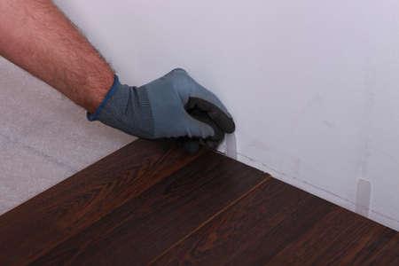dilate: Man installing parquet flooring