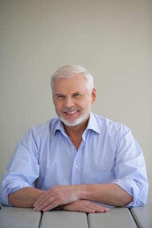 Senior man sitting at an outdoor table photo