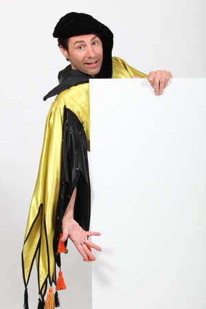 harlequin clown in disguise: Man dressed as court jester holding message board Stock Photo