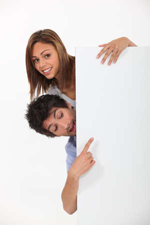 Surprised couple with a board left blank for your message Stock Photo - 22879084