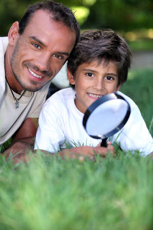 investigative: Father and son examining the grass with a magnifying glass