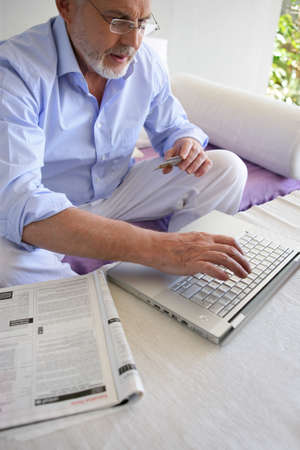 Gray-haired man shopping on-line photo