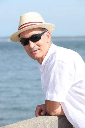 leaning by barrier: Portrait of elderly man Stock Photo