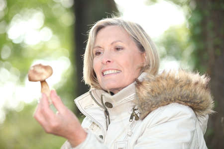 Woman with a mushroom in a forest Stock Photo - 22879099