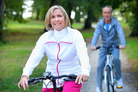 Senior couple enjoying a bicycle ride photo