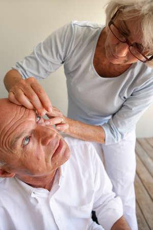 lentes contacto: Esposa ayudar marido con lentes de contacto Foto de archivo