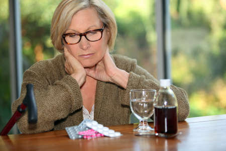 analgesics: Woman sat in front of medication Stock Photo