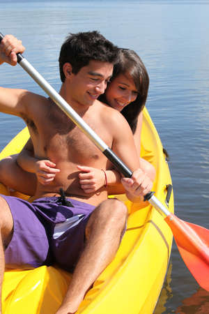 15: Teenage girl hanging onto her boyfriend while kayaking Stock Photo