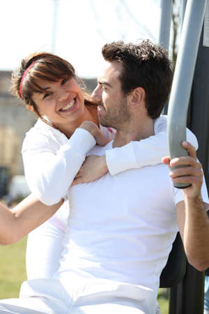 Couple using outdoor gym equipment photo