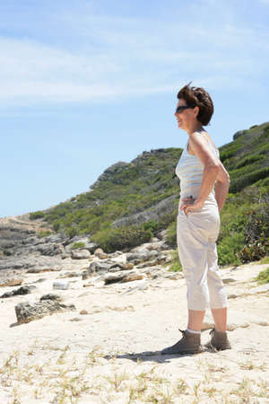 Middle-aged woman standing on a beach photo
