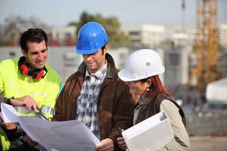 Foreman y dos colegas examinar los planes Foto de archivo - 22840369