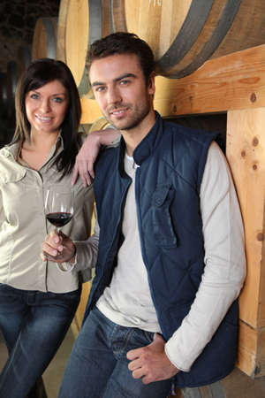 Couple standing in a wine cellar photo