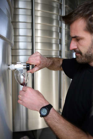 Man pouring wine from a stainless steel vat photo