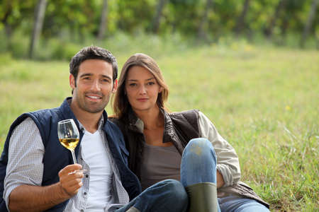 Couple having a glass of wine by a vineyard photo