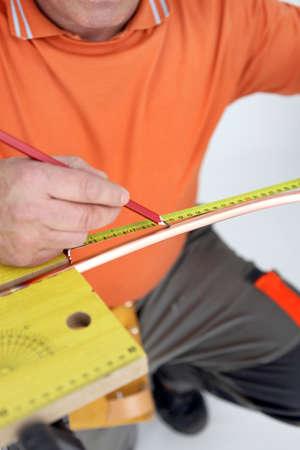 Laborer measuring copper tube