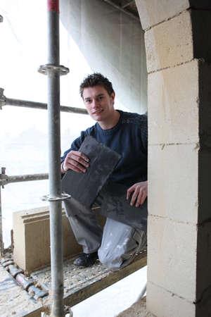 refurbishing: Giovane operaio ristrutturazione di un edificio Archivio Fotografico