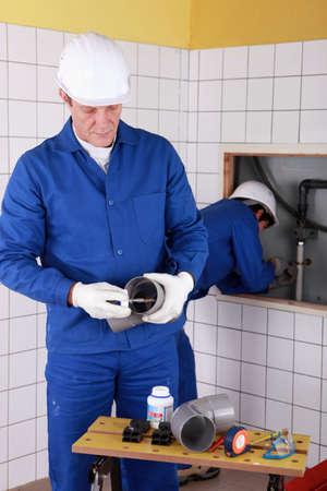 plastic conduit: Two plumbers working in a bathroom