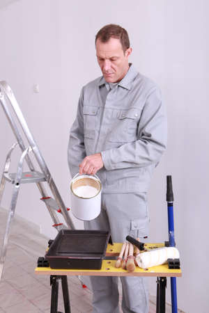 45 years old house painter is putting paint in a box photo