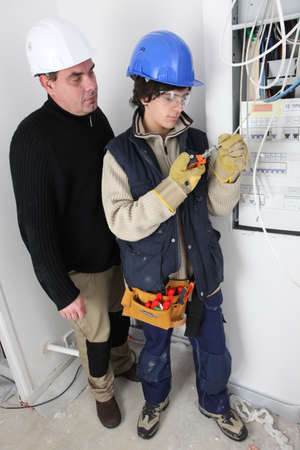 Electrician and apprentice by fusebox photo