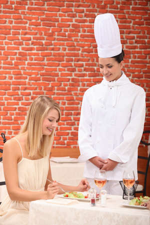 young woman congratulating female chef in restaurant photo
