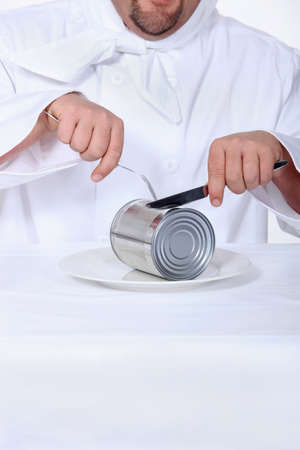 portly: Chef pretending to cut tin can with knife and fork Stock Photo