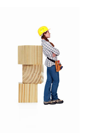Female carpenter standing by large wooden blocks photo