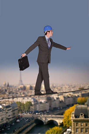 Businessman walking on a tightrope Stock Photo - 23811024