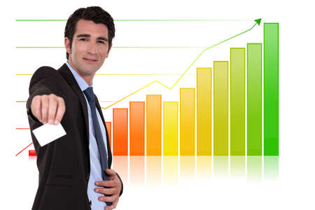 Businessman with calling card standing by bar chart photo
