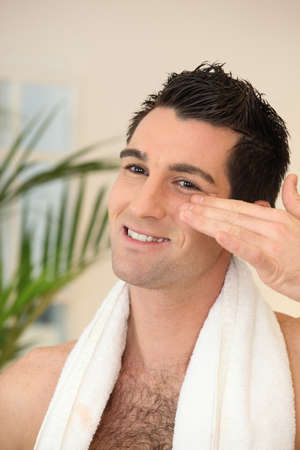 Man applying moisturizer photo