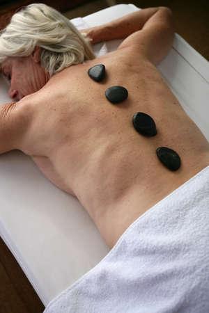 meridians: Older woman enjoying a hot stone massage