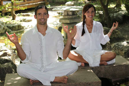 Couple meditating in garden photo
