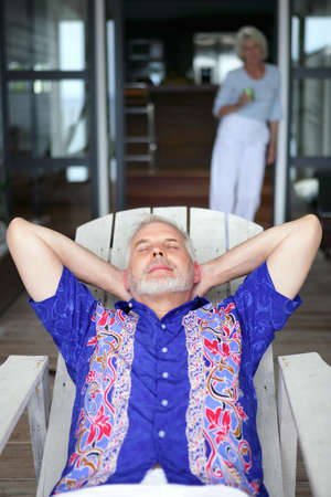 55 60 years: Senior man relaxing on a veranda Stock Photo