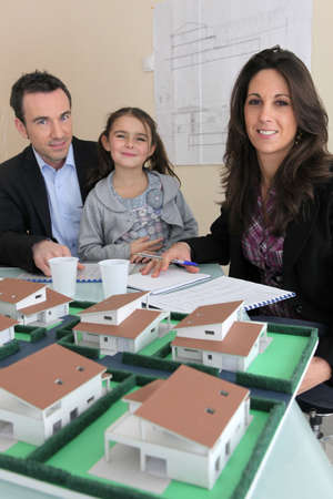 Architect presenting model housing to a potential client and his daughter photo