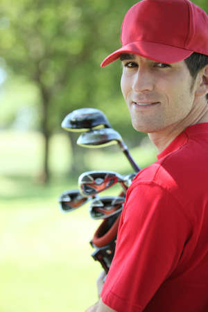 Golfer holding golf clubs smiling  photo