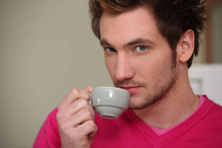 Young man drinking an expresso photo