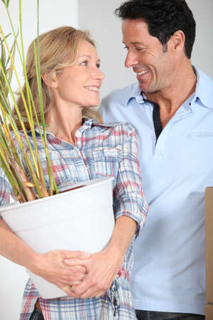 Couple smiling with plant photo