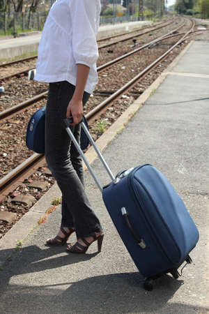 Woman waiting on a train platform with a suitcase photo