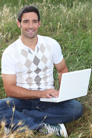 Man sat in field using laptop computer photo