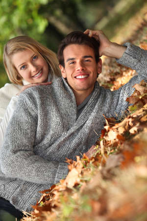 Couple laid in fallen leaves photo