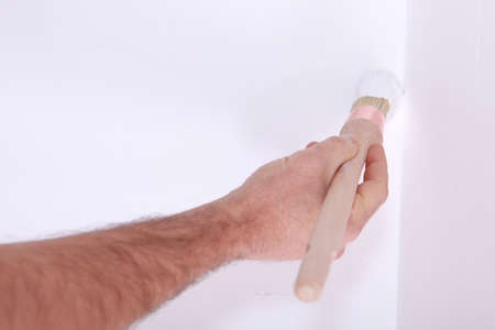 Man painting wall with brush photo