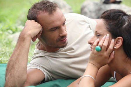 Couple lying on a blanket on the grass photo