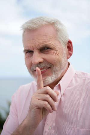 Senior man making shush gesture