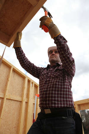 Builder putting up a wooden house photo