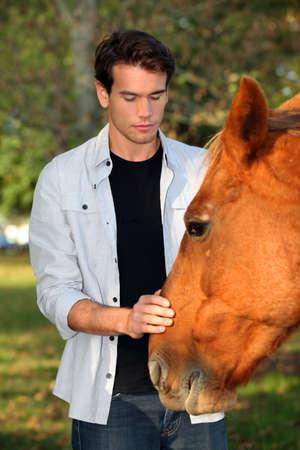 uomo a cavallo: Giovane uomo accarezza un cavallo Archivio Fotografico