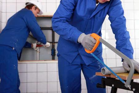 Plumber sawing grey pipe photo