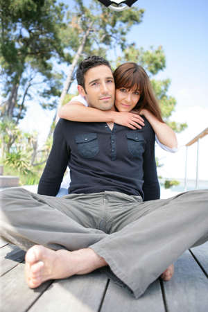 Couple sitting on a wooden deck photo