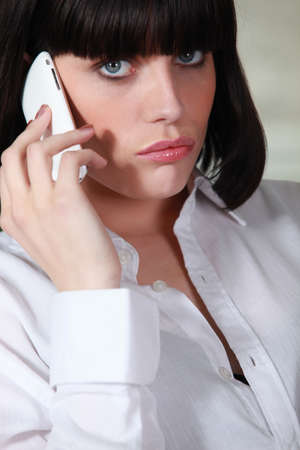 Upset brunette making telephone call photo