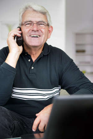 Senior man laughing whilst on the telephone photo