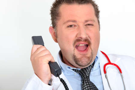 moon-faced doctor with stethoscope arguing on phone Stock Photo - 23874009